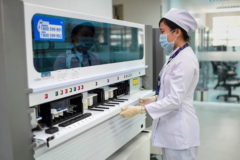 Nhân viên y tế đang sử dụng máy xét nghiệm máu